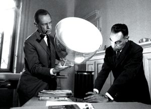 The brothers Achille and Pier Giacomo Castiglioni with the Taccia table lamp.