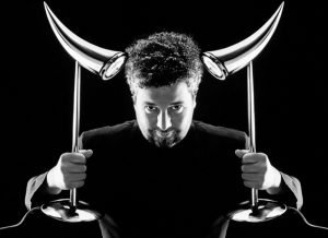 The designer Philippe Starck holds an Ara table lamp in his hand on the left and right.